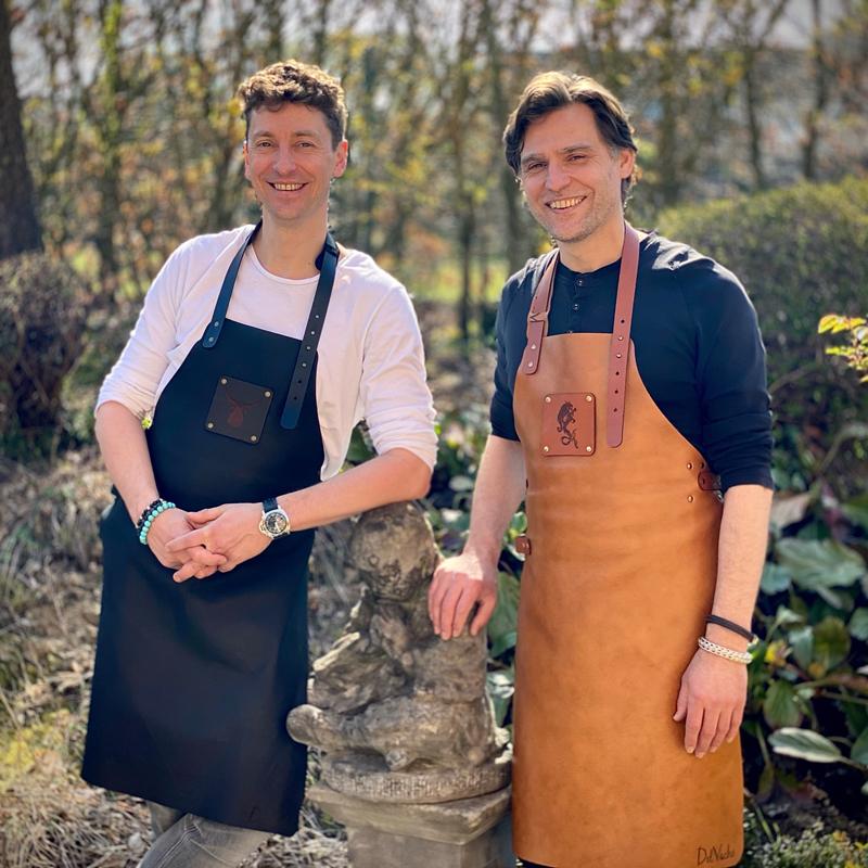 Christophe Saeys à droite et Gunther Willems à gauche avec des tabliers en cuir Delvache : ce sont les fondateurs de cette marque de tablier élégant pour barbecue