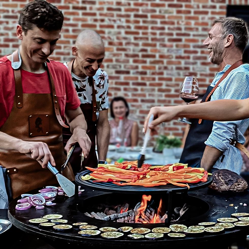 Barbecue en famille : on peut voir 4 hommes en train de faire un barbecue pour un déjeuner en famille. Ils sont tous vêtu du tablier en cuir Delvache. Moment de convivialité, de bonheur et de rires